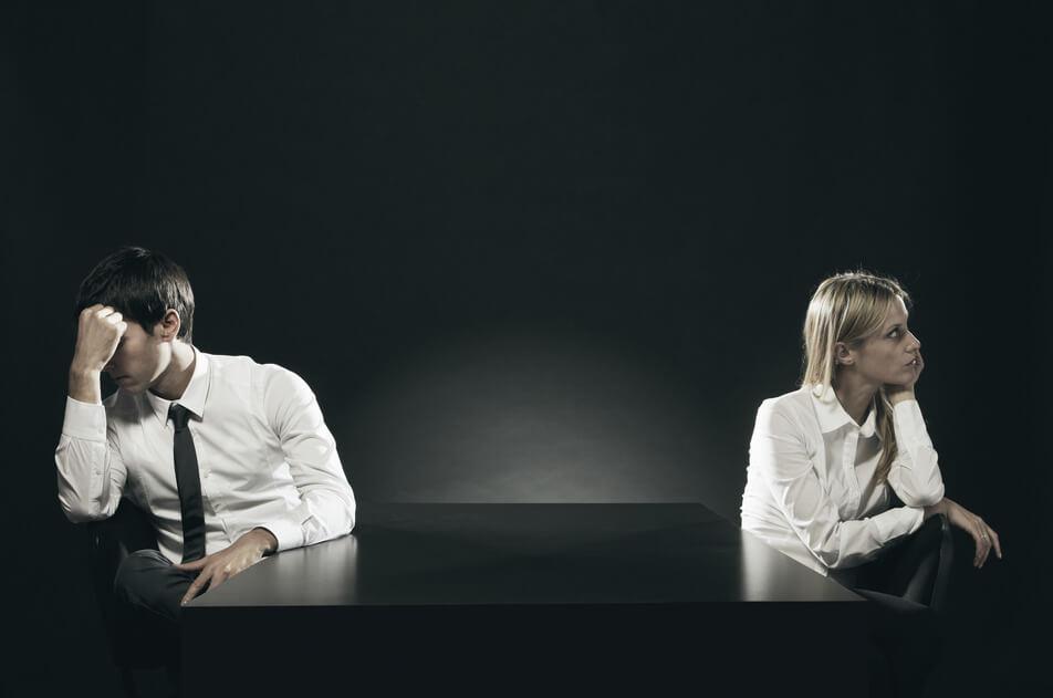 Ein Paar welches nach einem Streit an einem Tisch sitzt.
