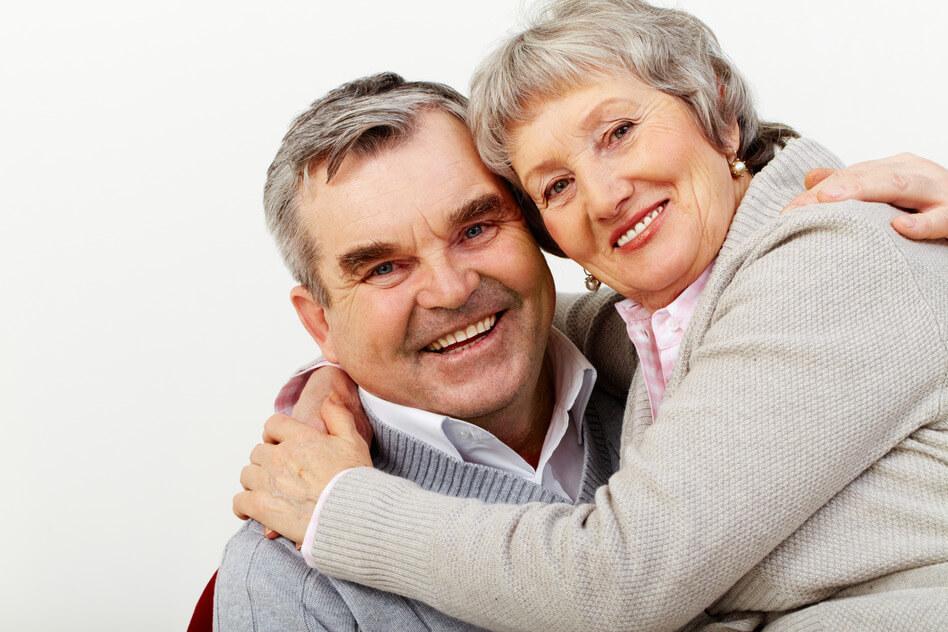 Ein älteres Paar welches sich in den Armen hält.